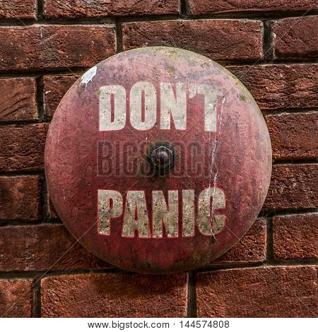 Isolated Rustic Vintage Red Alarm Bell With The Words Don't Panic In White Against A Red Brick Wall