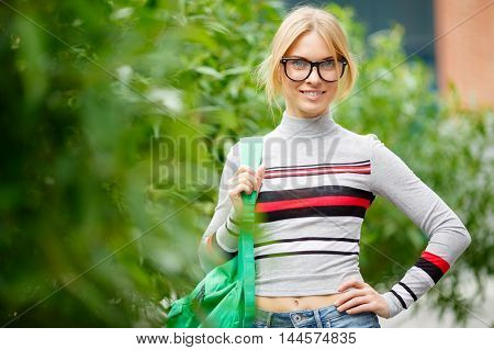blonde with glasses and backpack on shoulder posing before Bush