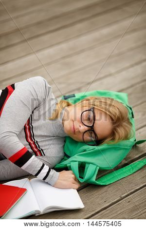 sleeping female student with book on wooden floor outdoors