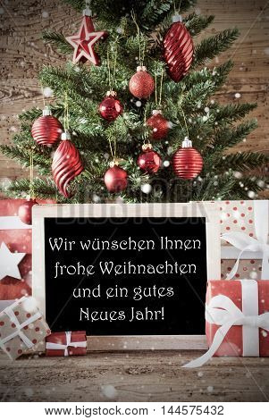 Nostalgic Card For Seasons Greetings. Christmas Tree With Balls. Gifts Or Presents In The Front Of Wooden Background. Chalkboard With German Text Frohe Weihnachten Means Merry Christmas