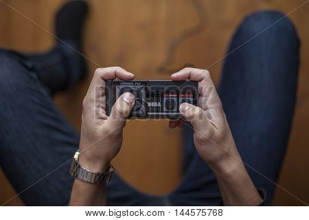 Gothenburg, Sweden - January 7, 2015: A shot from above of a young mans hands holding an old game pad for the Sega Master System video game console, released in the 1980s.