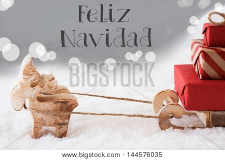 Moose Is Drawing A Sled With Red Gifts Or Presents In Snow. Christmas Card For Seasons Greetings. Silver Background With Bokeh Effect. Spanish Text Feliz Navidad Means Merry Christmas