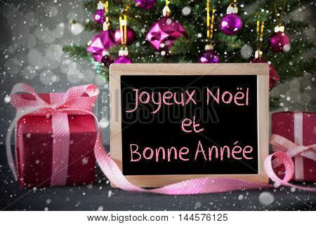 Chalkboard With French Text Joyeux Noel Et Bonne Annee Means Merry Christmas And Happy New Year. Christmas Tree With Rose Quartz Balls, Snowflakes And Bokeh Effect.Gifts In Front Of Cement Background.