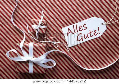 Two Gifts Or Presents With White Ribbon. Red And Brown Striped Wrapping Paper. Christmas Or Greeting Card. Label With German Text Alles Gute Means Best Wishes