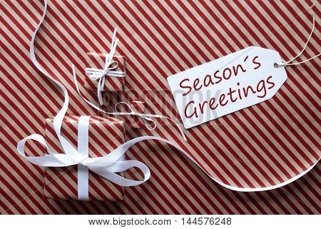 Two Gifts Or Presents With White Ribbon. Red And Brown Striped Wrapping Paper. Christmas Or Greeting Card. Label With English Text Seasons Greetings