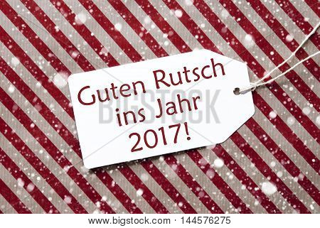 One Label On A Red And Brown Striped Wrapping Paper. Textured Background With Snowflakes. Tag With Ribbon. English Text Guten Rutsch Ins Jahr 2017 Means Happy New Year