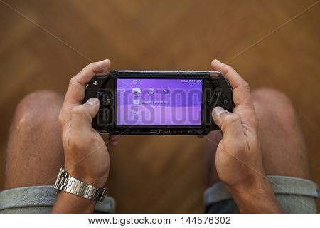 Gothenburg, Sweden - January 25, 2015: A Playstation Portable in the hands of a young man. The Playstation Portable, also referred to as PSP is a handheld game console developed by Sony Corporation.