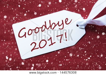 One White Label On A Red Textured Background. Tag With Ribbon And Snowflakes. English Text Goodbye 2017 For Happy New Year