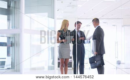Business woman standing in foreground in office .