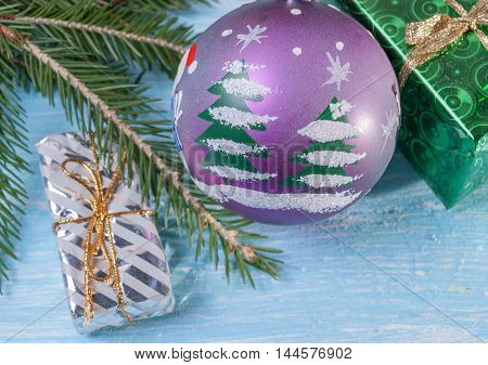 Gifts under fir branch and Christmas ball. Festive background