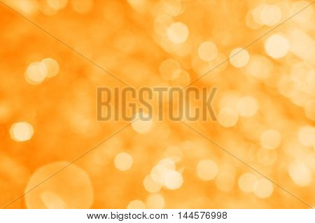 Abstract orange background with white bokeh and patches of light