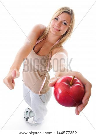 Woman plus size large happy girl on weight scale with apple measuring tape celebrating weightloss progress after diet thumb up gesture. Healthy lifestyles concept