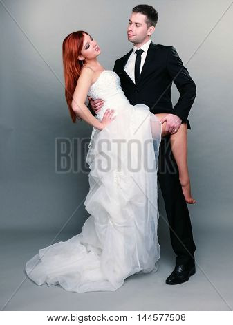 Wedding day. Portrait of happy married couple red haired sexy bride and groom in full length studio shot on gray background