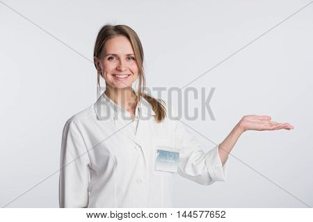 Young doctor woman or nurse presenting and showing copy space for product or text. Caucasian female medical professional isolated on white background