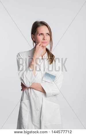 Thoughtful, Young Asian female doctor looking away isolated on white background.