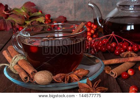 Autumn hot tea with spices and berries in glass cup and teapot on wooden background