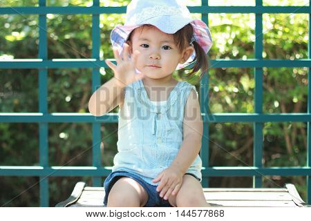 Japanese girl sitting on the bench (1 year old)