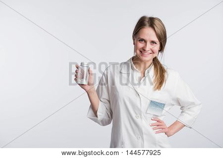 Young female doctor presenting a white unlabeled bottle or recipient of pills.