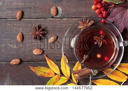 glass cup of hot autumn tea with spices and berries and autumn leaves on rustic wooden background. top view