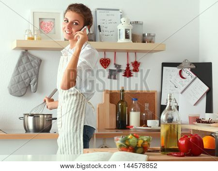 Portrait a smiling woman with phone in kitchen at home .