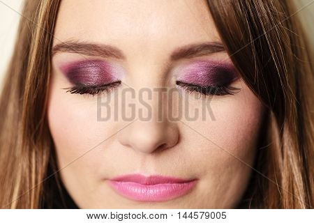 Woman long straight hair closed eyes with colorful shadows violet dark color makeup closeup