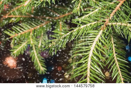 Christmas tree branches with toys with falling snowflakes