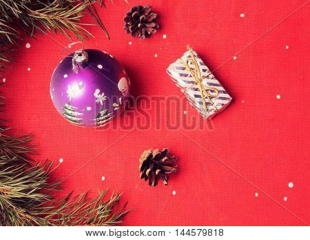 Christmas balls branches and cones on a red background.