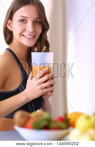 Girl sitting in the kitchen on the desk with fruit and glasses with juice.