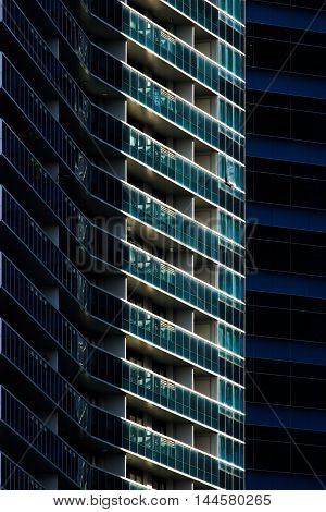 Abstract of blue glass balconies and windows of modern building in lights and shadows.