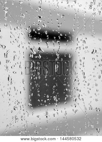 Many water drops glowing on a glass through which a dark window is seen.