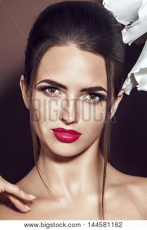 Beautiful young model with red lips and red manicure