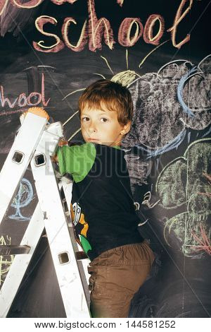 little cute real boy at blackboard in classroom painting, back to school close up