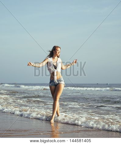 young pretty blond woman at seacoast walking relaxing, fashion lady at sunset, people on summer vacation concept