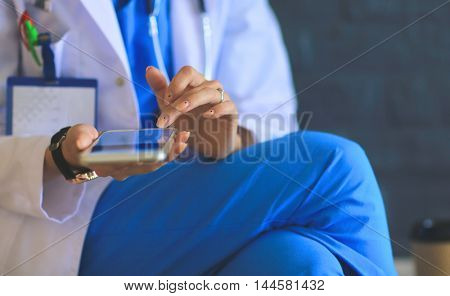 Young woman doctor sitting with your phone