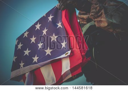 Folded American Flag in Soldier Hands Closeup Photo