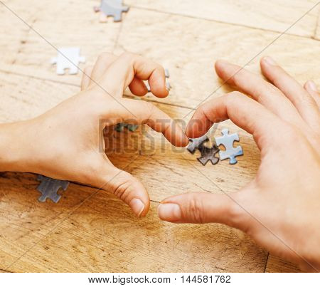 little kid playing with puzzles on wooden floor together with parent, lifestyle people concept, loving hands to each other, warm wooden interior