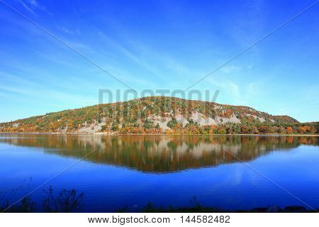 Autumn  covered hillside reflected in glass smooth lake water