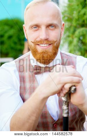 Smiling blonde guy in bow tie and cane in hands