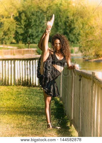 Latino dancer in a park with raised leg
