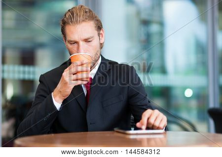 Portrait of a businessman using his tablet computer in a coffee shop