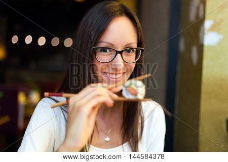 Cute girl eating sushi in a japanese restaurant