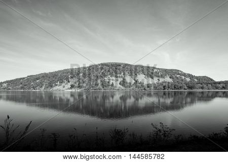 black and white forest covered ridge reflected on smooth lake surface