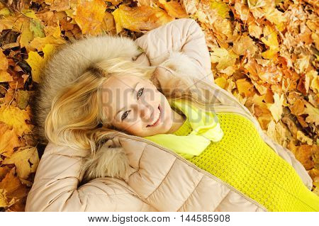 Smiling happy young blonde woman lying in autumn leaves, looking at camera, top view, healthy lifestyle concept, outdoor in autumn park