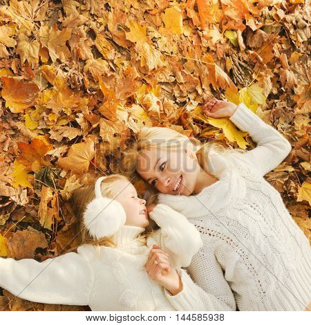 Mother and daughter have a fun in autumn park, lying in yellow autumn foliage and looking each other, top view, happy lifestyle