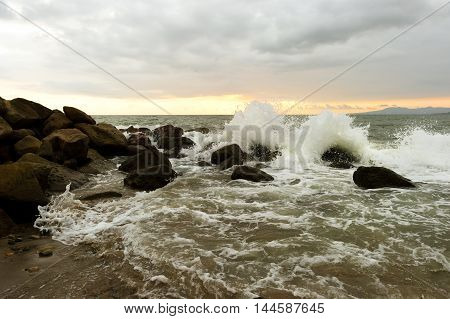 Waves crashing is an ocean wave rushing to shore hitting sea rocks and shooting up into the air as ocean spray.