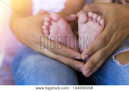 Parent holding baby feet with heart shape hands