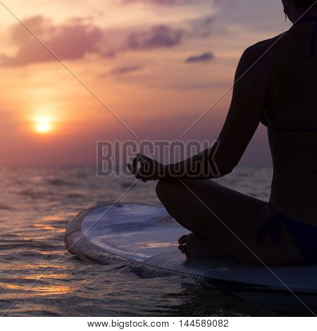 Instagram like shot of a woman practicing meditating on a paddle board.