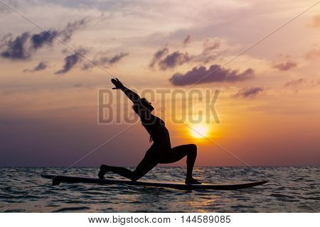 Woman practicing SUP yoga at sunset