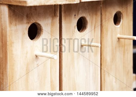 Several wooden birdhouses in a row background. A few wood bird houses for sale backdrop