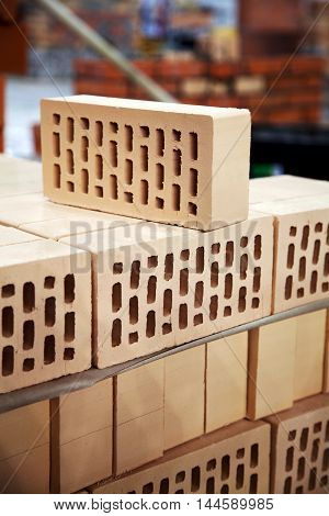 New hollow bricks stacked at warehouse for sale. Lot of yellow clay bricks close-up